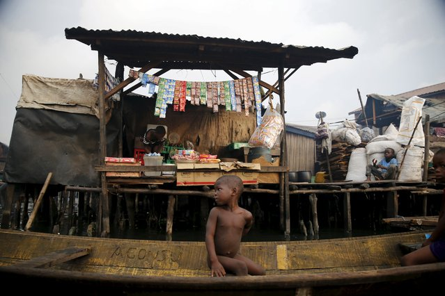 A boy sits in a canoe in front of a shed built on a raft in the Makoko fishing community on the Lagos Lagoon, Nigeria February 29, 2016. Makoko, a vast slum of houses on stilts in a Lagos lagoon, now boasts a new school – pyramid-shaped, floating and capable of withstanding the waterways' extreme weather, it is a beacon of hope for the nearly 100,000 Nigerians who live there.  (Photo by Akintunde Akinleye/Reuters)