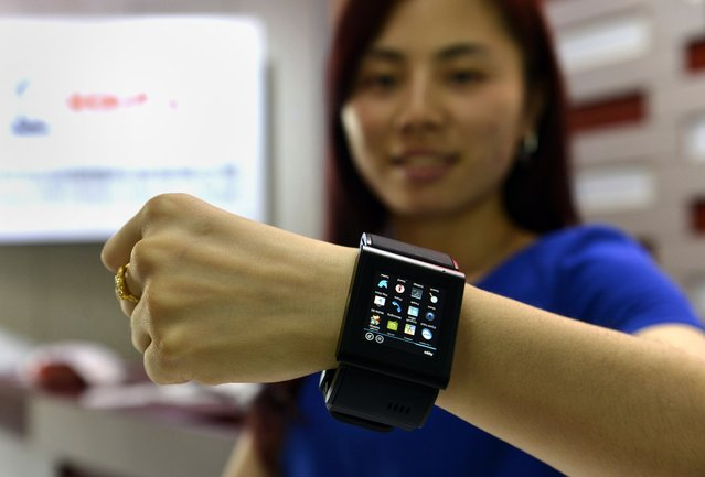 This picture taken on April 22, 2015 shows a Chinese promoter posing with a local alternative to the Apple Watch at a factory producing thousands every day in Shenzhen, in southern China's Guangdong province.  The much-hyped Apple Watch goes on sale on April 24, but Chinese factories are already churning out cheaper alternatives to the apparent delight of local consumers. (Photo by AFP Photo/Stringer)