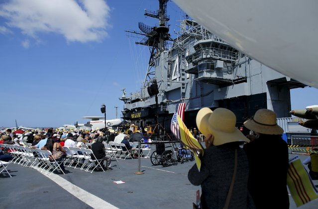 Visiting members of the Vietnamese community attend a ceremony on the flight deck of the USS Midway as the ship commemorates the 40th Anniversary of Operation Frequent Wind and the fall of Saigon in San Diego, California, United States April 26, 2015. (Photo by Mike Blake/Reuters)