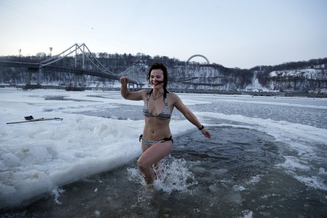 An Orthodox believer plunges in icy water in the Dnipro River during celebrations of the Epiphany in Kiev, Ukraine, Tuesday, January 19, 2016. Orthodox believers celebrate the holiday of the Epiphany on Jan. 19, and traditionally bathe in holes cut through thick ice on rivers and ponds to cleanse themselves with water deemed holy for the day. (Photo by Efrem Lukatsky/AP Photo)