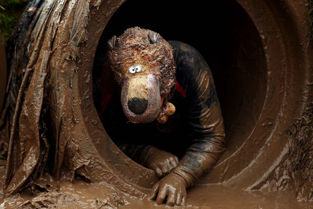 A competitor crawls through a tunnel during the Tough Guy Challenge, which claims to be the world's most demanding one-day survival ordeal, on January 26, 2014. First staged in 1987, the Tough Guy Challenge has been widely described as one of the hardest races of its type, with up to one-third of the starters failing to finish in a typical year. (Photo by Bryn Lennon/Getty Images)