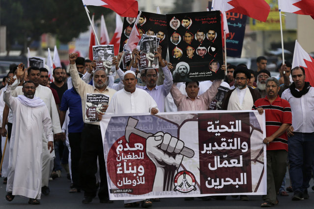A small group of Bahraini men, carrying national flags and signs, march quickly between police patrols, on the lookout for violators of a protest ban, in Manama, Bahrain, Friday, May 1, 2015. (Photo by Hasan Jamali/AP Photo)