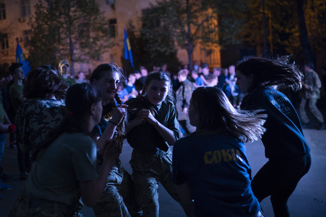 In this April 21, 2018 photo, members of the nationalist group Sokil, the youth wing of the Svoboda party, bump into each other during a concert in Kiev, Ukraine. (Photo by Felipe Dana/AP Photo)