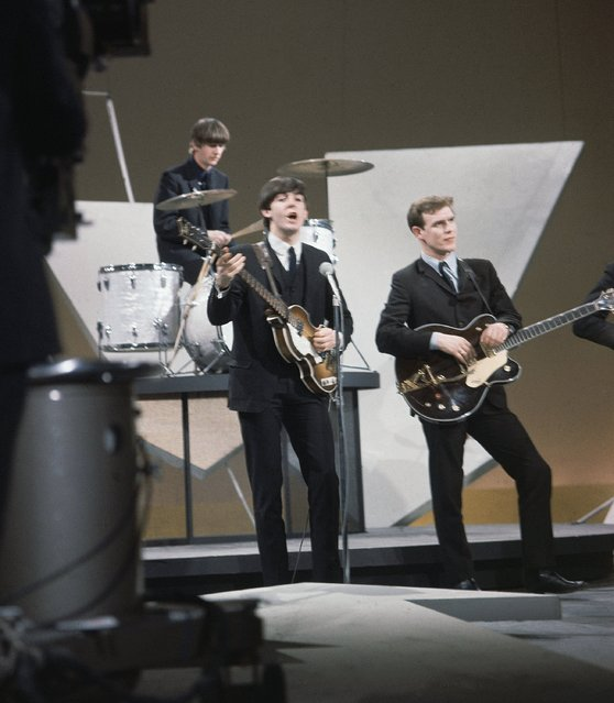 "British rock band the Beatles areshown during rehearsals on the set of the ""Ed Sullivan Show"" in New York, February 9, 1964.  On drums is Ringo Starr, bassist and singer is Paul McCartney, and standing in for George Harrison is an unidentified studio worker. (Photo by AP Photo)"
