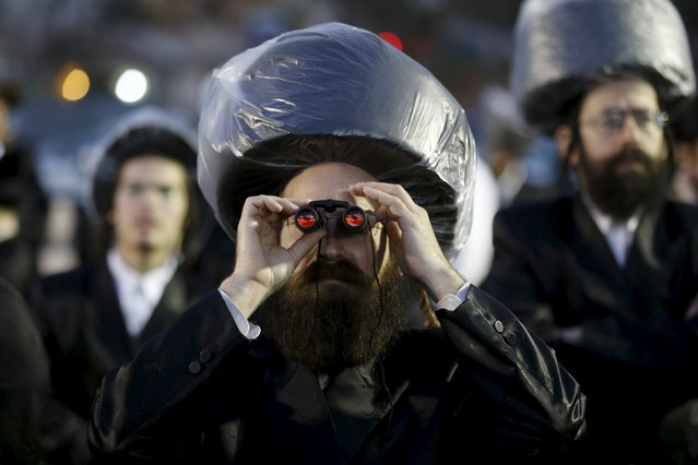 An ultra-Orthodox Jewish man uses binoculars during the wedding ceremony the grandson of Rabbi Yosef Dov Moshe Halberstam, religious leader of the Sanz Hasidic dynasty and the granddaughter of the religious leader of Toldos Avraham Yitzchak Hasidic dynasty, in Netanya, Israel March 15, 2016. (Photo by Baz Ratner/Reuters)