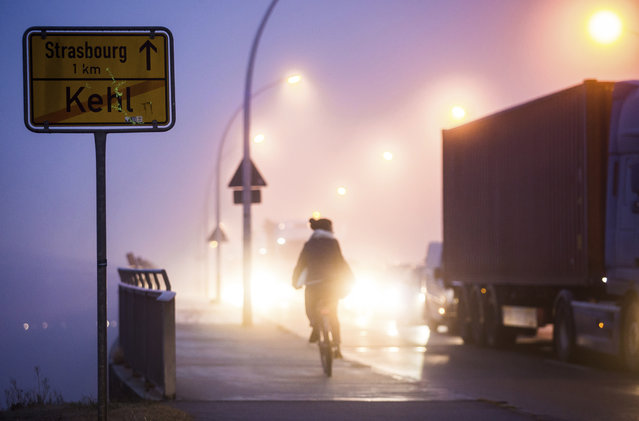 A cyclist crosses the bridge as police control the border between Germany and France in Kehl, southern Germany, Wednesday, December 12, 2018 the morning  after a suspected extremist sprayed gunfire at one of Europe's most famous Christmas markets in the eastern city of Strasbourg, killing three and wounding at least 13. (Photo by Christoph Schmidt/DPA via AP Photo)