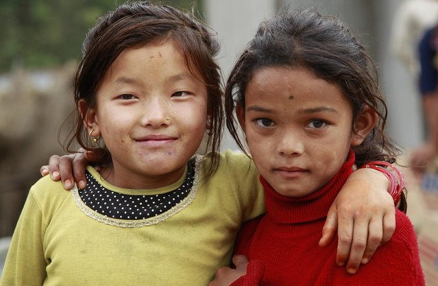 Pashmina Ghaley, 10, left, and her friend Ramina Bhujel, 10, pal around in the destroyed village of Balua, near the epicenter of Saturday's massive earthquake, in the Gorkha District of Nepal, Thursday, April 30, 2015. (Photo by Wally Santana/AP Photo)