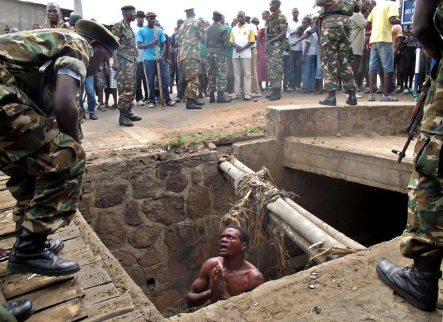 "A man begs for help from the military from a gutter where he had hid himself on May 7, 2015 to escape a lynching by a mob at the Cibitoke district of Burundi capital, Bujumbura. The man suspected to be an ""Imbonerakure"", or member of the Youth League of Burundi's ruling party was finally saved by the army. At least three people were killed in clashes in Burundi today in protests over the president's bid for a third term. (Photo by Aymeric Vincenot/AFP Photo)"