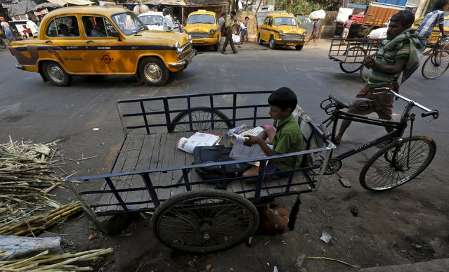 Rahul Shaw, 10, reads a textbook in his father's rickshaw before he goes to school in Kolkata, India, March 9, 2016. Shaw said he studies in a government-run school that gives him free meals. He wants to become a doctor and treat people for free. Some people in Kolkata earn a living by selling second-hand clothes, driving rickshaws or in the city's food markets. Those too poor to afford a home of their own sleep where they work, helping people who moved to the city to find work to send money back home. Outside working hours residents of the city formerly called Calcutta might enjoy a game of chess or carrom, while children play soccer with friends. (Photo by Rupak De Chowdhuri/Reuters)