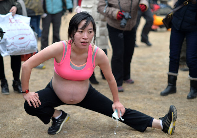 An expectant mother warms up during the annual 3.5 km undie run at Olympic Forst Park on February 23, 2014, in Beijing, China. (Photo by ChinaFotoPress/ChinaFotoPress via Getty Images)