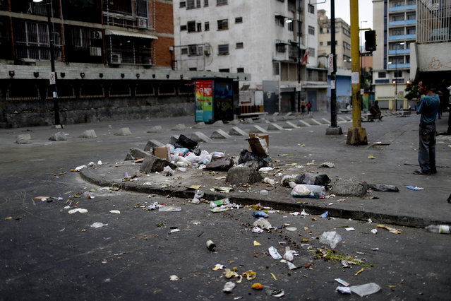 Garbage lays scattered on the pavement in Caracas, Venezuela, early Monday, March 25, 2019. The poor and hungry scour through household trash, scattering it across street corners before it's collected, grabbing anything they can use or eat. (Photo by Natacha Pisarenko/AP Photo)