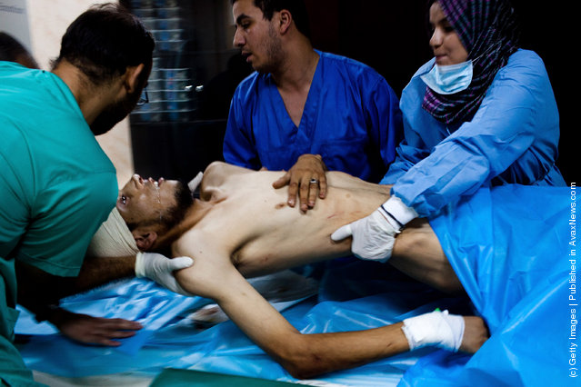 A Libyan Rebel fighter is lifted by medical staff for a cat-scan to ascertain damage to his brain, after receiving a headshot from a pro-Gaddafi loyalist sniper