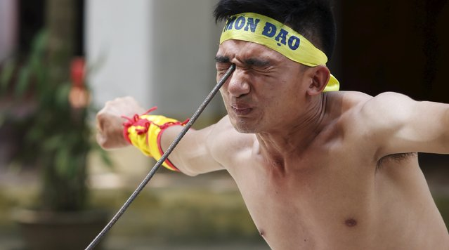 Vietnamese student Le Duc Thang, 24, bends a metal spear by pressing it into the area around his right eye as he performs during a showcase of traditional Thien Mon Dao kung fu at Du Xa Thuong village, southeast of Hanoi, Vietnam May 10, 2015. (Photo by Reuters/Kham)
