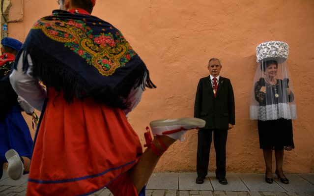 """A participant, right, of """"Prioresses Procession"""" takes part in a ceremony in honor of Domingo de La Calzada Saint (1019-1109), who helped poor people and pilgrims, in Santo Domingo de La Calzada, northern Spain, Friday, May 10, 2019. Every year during spring season, """"Las Prioras"""" (Prioresses) hold on their head a basket covered with white cloth and dress in black while they walk past along of this old village in honor of the saint. (Photo by Alvaro Barrientos/AP Photo)"""
