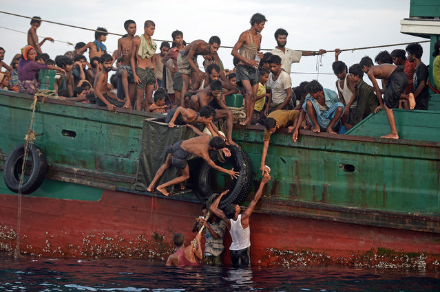 Rohingya migrants pass food supplies dropped by a Thai army helicopter to others aboard a boat drifting in Thai waters off the southern island of Koh Lipe in the Andaman sea on May 14, 2015. A boat crammed with scores of Rohingya migrants – including many young children – was found drifting in Thai waters on May 14, with passengers saying several people had died over the last few days. (Photo by Christophe Archambault/AFP Photo)
