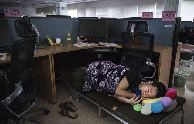 A Huawei employee watches a program on his smartphone as he rests in his cubicle in the research and development area after lunch at the Bantian campus on April 12, 2019 in Shenzhen, China. Huawei is Chinas most valuable technology brand, and sells more telecommunications equipment than any other company in the world, with annual revenue topping $100 billion U.S. Headquartered in the southern city of Shenzhen, considered Chinas Silicon Valley, Huawei has more than 180,000 employees worldwide, with nearly half of them engaged in research and development. In 2018, the company overtook Apple Inc. as the second largest manufacturer of smartphones in the world behind Samsung Electronics, a milestone that has made Huawei a source of national pride in China. While commercially successful and a dominant player in 5G, or fifth-generation networking technology, Huawei has faced political headwinds and allegations that its equipment includes so-called backdoors that the U.S. government perceives as a national security. U.S. authorities are also seeking the extradition of Huaweis Chief Financial Officer, Meng Wanzhou, to stand trial in the U.S. on fraud charges. Meng is currently under house arrest in Canada, though Huawei maintains the U.S. case against her is purely political. Despite the U.S. campaign against the company, Huawei is determined to lead the global charge toward adopting 5G wireless networks. It has hired experts from foreign rivals, and invested heavily in R&D to patent key technologies to boost Chinese influence. (Photo by Kevin Frayer/Getty Images)