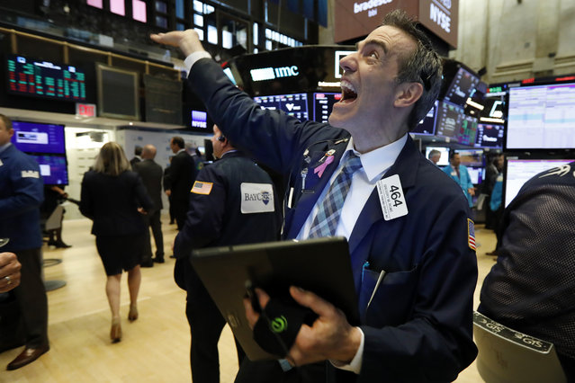 Trader Gregory Rowe laughs with fellow traders as he works on the floor of the New York Stock Exchange, Wednesday, May 1, 2019. Stocks are opening higher on Wall Street after several big U.S. companies reported earnings that were better than analysts were expecting. (Photo by Richard Drew/AP Photo)
