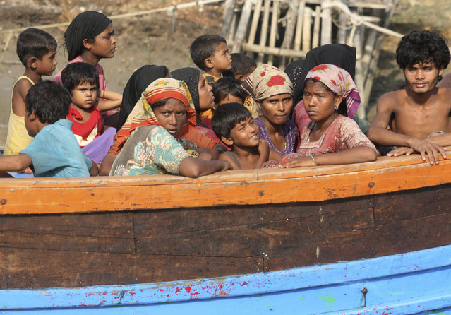 Rescued migrants sit on an Acehnese fishing boat upon arrival in Simpang Tiga, Aceh province, Indonesia, Wednesday, May 20, 2015. Hundreds of migrants stranded at sea for months were rescued and taken to Indonesia, officials said Wednesday, the latest in a stream of Rohingya and Bangladeshi migrants to reach shore in a growing crisis confronting Southeast Asia. (Photo by Binsar Bakkara/AP Photo)