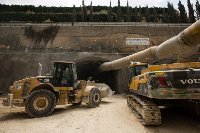 Construction machinery and vehicles are seen at the entrance to the construction site of an underground tunnel designated for traditional Jewish burial at the Givat Shaul cemetery, on May 14, 2015, in Jerusalem, Israel. (Photo by David Vaaknin/The Washington Post)