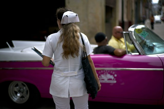 A nurse walks down the street where a classic American car carries tourists in Havana, Cuba, Wednesday, April 10, 2019. (Photo by Ramon Espinosa/AP Photo)