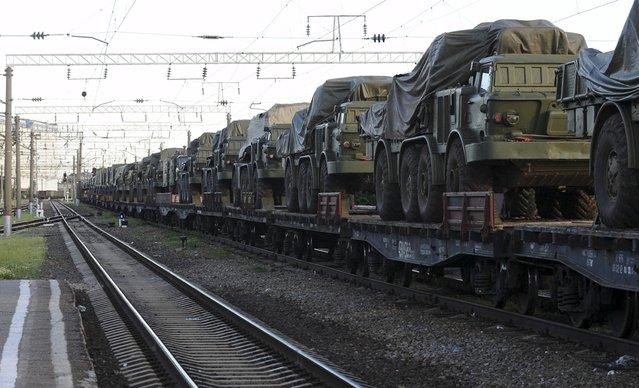 Multiple launch rocket systems and military trucks are seen on freight train platforms in the Russian southern town of Matveev Kurgan ,near the Russian-Ukrainian border in Rostov region, Russia, May 23, 2015. (Photo by Reuters/Stringer)