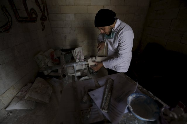 Khamis, 24, files an artificial limb inside a workshop in the rebel-controlled area of Maaret al-Numan town in Idlib province, Syria March 20, 2016. (Photo by Khalil Ashawi/Reuters)
