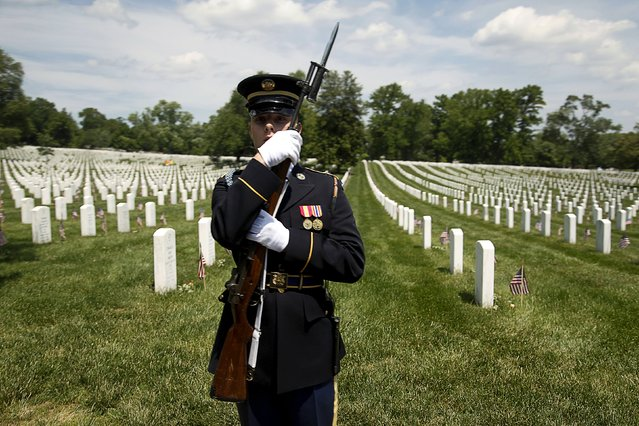 A member of an honor guard holds his rifle as the motorcade carrying U.S. President Barack Obama departs after he participated the Memorial Day observance at Arlington National Cemetery in Arlington, Virginia May 25, 2015. (Photo by Jonathan Ernst/Reuters)