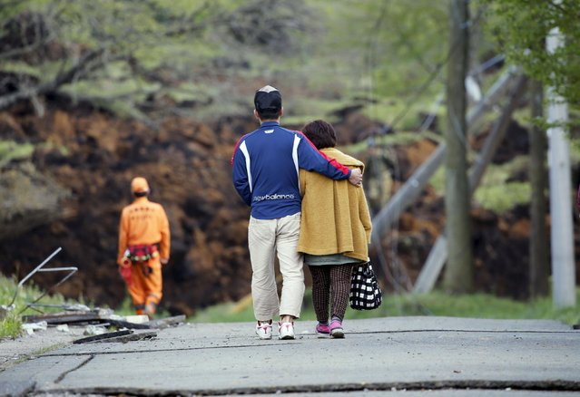 A son helps his mother as they leave from their collapsed house at a landslide site caused by an earthquake where his father is missing in Minamiaso town, Kumamoto prefecture, southern Japan, in this photo taken by Kyodo April 17, 2016. (Photo by Reuters/Kyodo News)