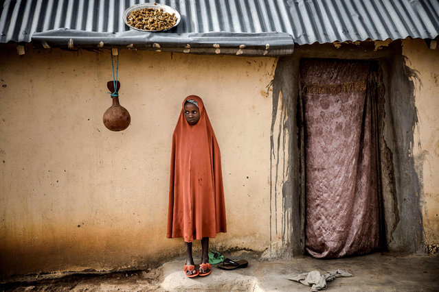 A Fulani girl waits outside her house at Kachia Grazing Reserve, Kaduna State, Nigeria, on April 16, 2019. Kachia Grazing Reserve is an area set aside for the use of Fulani pastoralist and it is intended to be the foci of livestock development. The purpose for the grazing reserves is the settlement of nomadic pastoralists and inducement to sedentarisation through the provision of land for grazing and permanent water as way to avoid conflict. (Photo by Luis Tato/AFP Photo)
