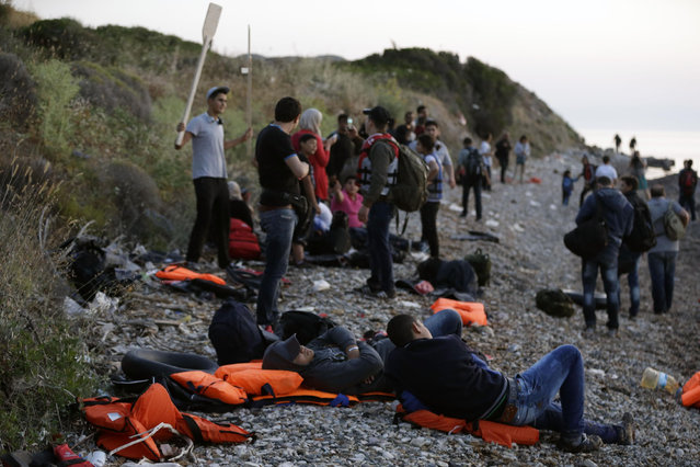 Syrian migrants rest as others take photographs after their arrival from Turkish coasts at a beach in Mytilene, on the northeastern Greek island of Lesvos, early Tuesday, June 16, 2015. Lesvos has been bearing the brunt of a huge influx of migrants from the Middle East, Asia and Africa crossing from the Turkish coast to nearby Greek islands. More than 50,000 migrants have arrived in Greece already this year, compared to 6,500 in the first five months of last year. (AP Photo/Thanassis Stavrakis)