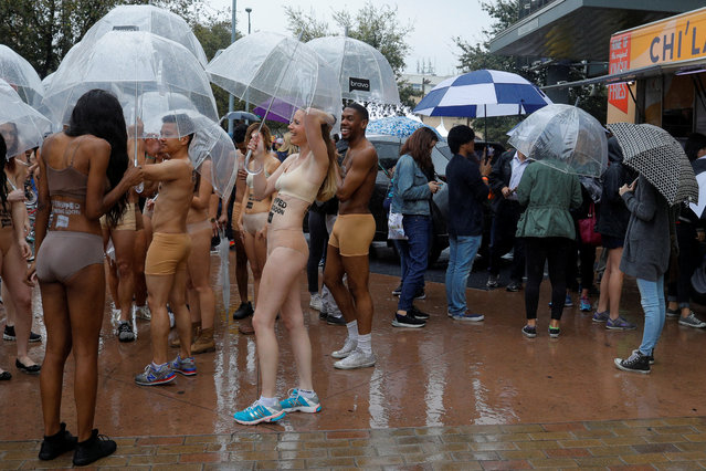 "People stripped of their clothes to promote the new Bravo series ""Stripped"" stand under umbrellas in the rain during the South by Southwest Music Film Interactive Festival 2017 in Austin, Texas, U.S., March 12, 2017. (Photo by Brian Snyder/Reuters)"