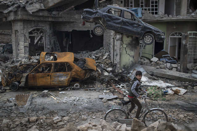 A boy rides his bike past destroyed cars and houses in a neighborhood recently liberated by Iraqi security forces, on the western side of Mosul, Iraq, Sunday, March 19, 2017. (Photo by Felipe Dana/AP Photo)