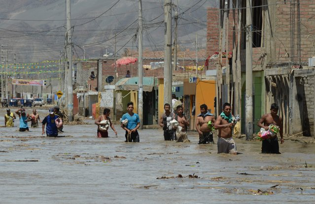 Local residents of the town of Huarmey, 300 kilometres north of Lima, wade through muddy water in the street on March 19, 2017 after a flash flood hit the evening before. (Photo by Cris Bouroncle/AFP Photo)