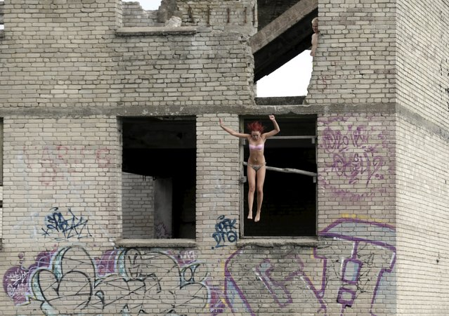A woman jumps into water from the roof of Murru prison, an abandoned Soviet prison, in Rummu quarry, Estonia, during hot weather July 4, 2015. (Photo by Ints Kalnins/Reuters)