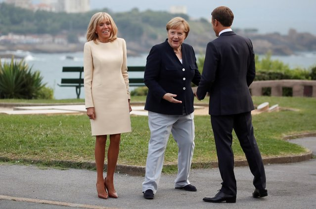 French President Emmanuel Macron and his wife Brigitte Macron welcome German Chancellor Angela Merkel at the G7 summit in Biarritz, France, August 24, 2019. (Photo by Christian Hartmann/Reuters)