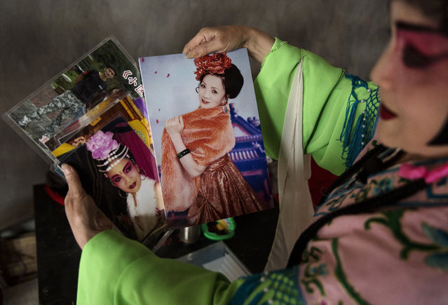 Sichuan Opera performer Lin Lijuan, 69 years, of the Jinyuan Opera Company displays old pictures of herself in costume before the group's performance for villagers at the Dongyue Temple on May 2, 2016 in Cangshan, Sichuan province, China. (Photo by Kevin Frayer/Getty Images)