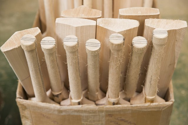 Part made cricket bats sit in a box at the Salix Cricket Bat Company in Langley, Britain July 6, 2015. Salix Cricket Bat Company use traditional tools and techniques to make cricket bats by hand. (Photo by Neil Hall/Reuters)
