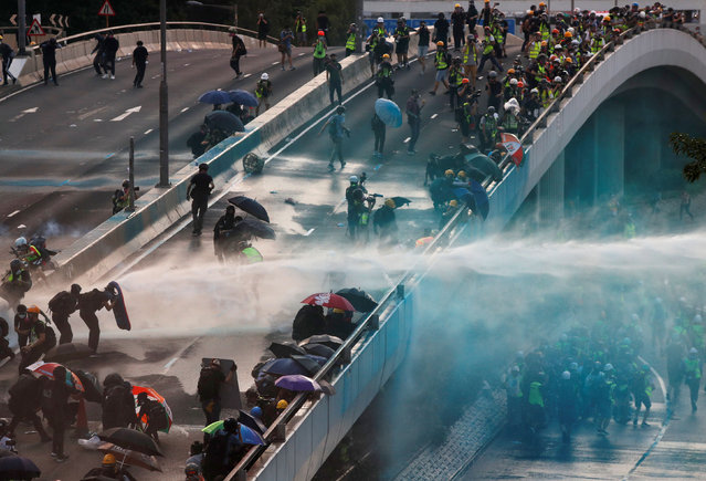 Anti-government protesters are sprayed with water cannon by the riot police during a demonstration near Central Government Complex in Hong Kong, China, September 15, 2019. (Photo by Jorge Silva/Reuters)