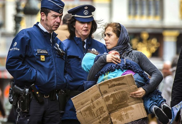 Police officers remove a woman and her child who were begging for money in front of the Grand Place in Brussels, Thursday, May 8, 2014. (Photo by Geert Vanden Wijngaert/AP Photo)