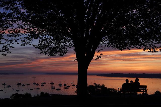 An early-rising couple is rewarded with a colorful sunrise over Casco Bay, Wednesday, August 21, 2019, in Portland, Maine. (Photo by Robert F. Bukaty/AP Photo)