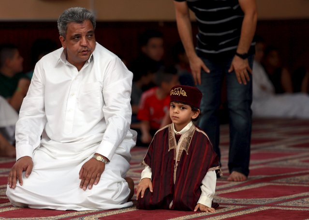 A boy waits for prayers with his father at a mosque during Eid al-Fitr to mark the end of Ramadan in Benghazi, Libya July 17, 2015. (Photo by Esam Omran Al-Fetori/Reuters)