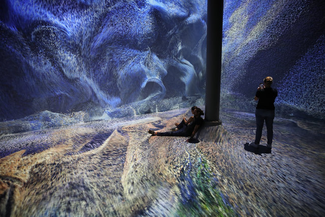 "People view the artwork ""Machine Hallucination"" by Turkish artist Refik Anadol at ARTECHOUSE in New York, United States on September 16, 2019. (Photo by Vural Elibol/Anadolu Agency via Getty Images)"