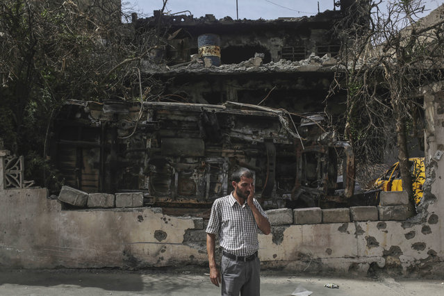 A man stands in front of a destroyed car and house in western Mosul, Thursday, May 11, 2017.  U.S.-backed Iraqi forces were moving to surround Mosul's Old City on Thursday, a week after launching a fresh push to drive Islamic State militants from areas they still hold. (Photo by Bram Janssen/AP Photo)