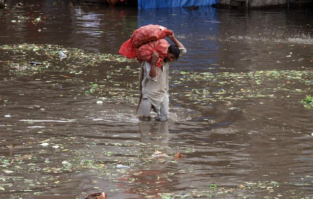 A Pakistani laborer carries sacks of potatoes while he wades through a flooded road caused by heavy rains in Lahore, Pakistan, Tuesday, July 21, 2015. (Photo by K. M. Chaudary/AP Photo)