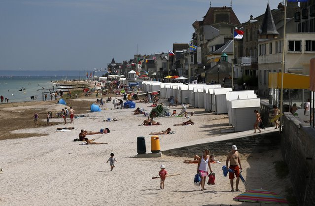 Tourists enjoy the sunshine on the former Juno Beach D-Day landing zone, where Canadian forces came ashore, in Saint-Aubin-sur-Mer, France, August 23, 2013. REUTERS/Chris Helgren