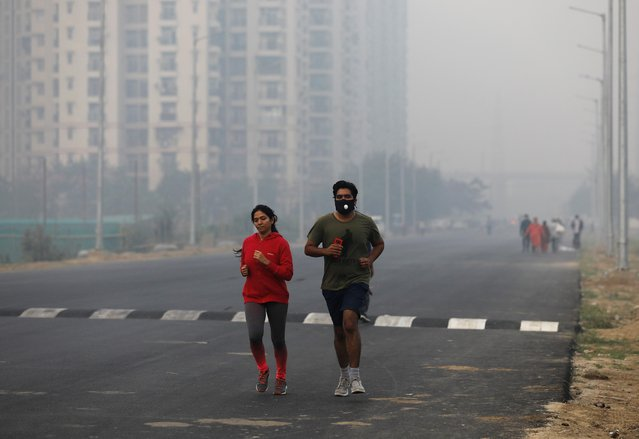 People jog on a foggy morning in Noida on the outskirts of New Delhi, India, November 14, 2019. (Photo by Anushree Fadnavis/Reuters)