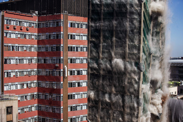 This picture taken on November 24, 2019 shows the Bank of Lisbon building imploding in Johannesburg, South Africa. Johannesburg CBD's iconic Bank of Lisbon building has been demolished after it was deemed structurally unfit following a 2018's fire which lasted three days and claimed the lives of three firefighters. (Photo by Michele Spatari/AFP Photo)