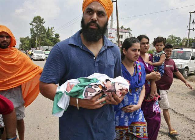 A local resident carries a newborn baby as he walks along with his family after police said they were evacuated from a hospital near the site of a gunfight at Dinanagar town in Gurdaspur district of Punjab, India, July 27, 2015. Heavily armed men dressed in military fatigues stormed a police station on Monday in India's northern frontier state of Punjab close to the border with Pakistan, killing six people and wounding several others. (Photo by Munish Sharma/Reuters)