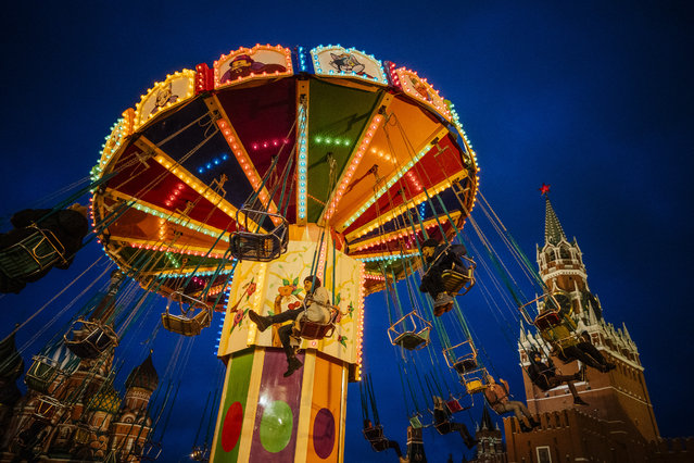 People ride a merry-go-round at the Christmas Market at the Red Square in Moscow, on December 16, 2019, as the Kremlin's Spasskaya Tower is seen in the background. (Photo by Dimitar Dilkoff/AFP Photo)