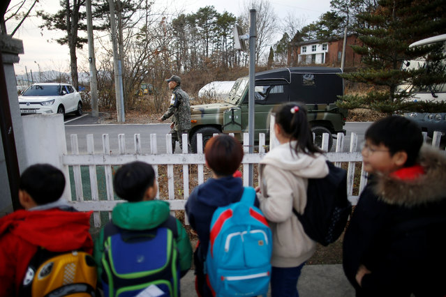 Children look at a soldier as they stand in a line to take a school bus at the Daesungdong Elementary School, a school inside the demilitarised zone separating the two Koreas, in Paju, South Korea, November 22, 2016. (Photo by Kim Hong-Ji/Reuters)
